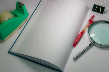Still life notebook and other stationery tools such as magnifying glass, pen, and adhesive tape in dim light  photo