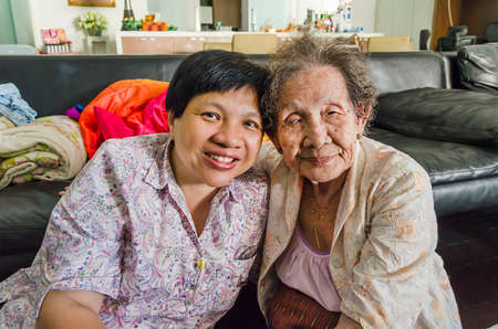Family Portrait of an Asian elder mother and daughter hold together in home scenery photo