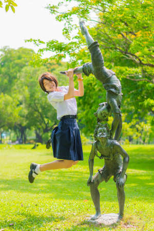 preteen  pure: Cute Thai schoolgirl is jumping with a statue in the park Stock Photo