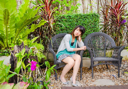 Cute Thai girl is sitting lonely on the garden chair