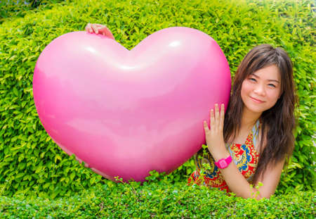 A cute Asian  Thai  girl is hugging giant pink heart in green leaves background photo