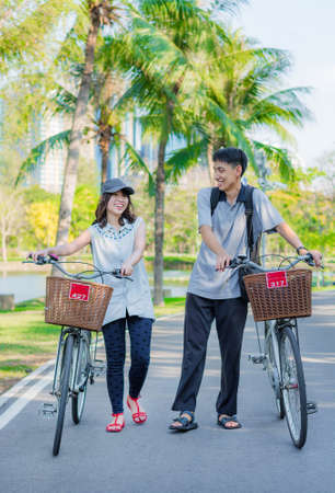A friend couple are walking and chatting with bicycle in the park photo