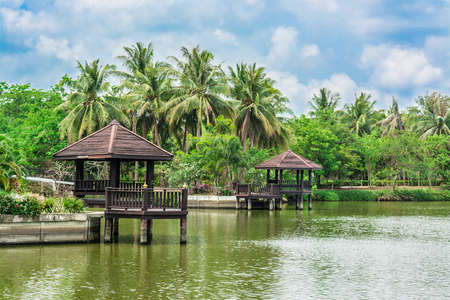 Beautiful riverside landscape with palm trees and resting pavilion in Thailand photo