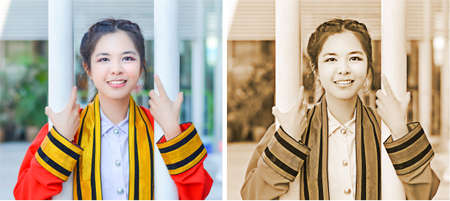 Graduate Thai college girl in academic gown is holding poles and smiling happily for the moment photo