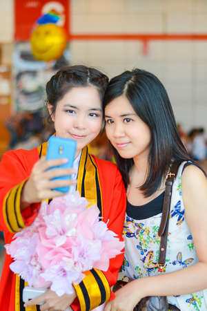 BANGKOK, THAILAND - 4 MAY 2013  Graduate Thai college student from King Mongkut s institution taking photograph with her friend for celebration on May 4, 2014  King Mongkut s technology institution is a famous university in Thailand