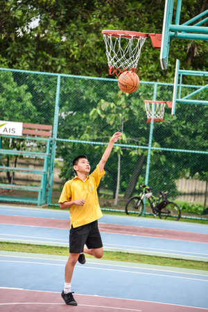 BANGKOK, THAILAND - 22 JULY 2014  Thai student is doing a layup shoot in public basketball court on July 22, 2014
