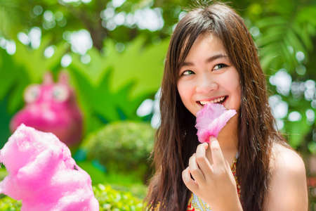 Cute Thai girl is eating pink candyfloss with joy