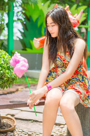 Cute Thai girl is sitting while holding pink candyfloss in summer concept photo