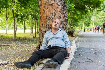 dode bladeren: Een dikke Aziatische man slapen onder de boom naast de straat Dit kan zo dronken begrip gebruiken Stockfoto