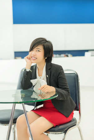 Cute Thai  Asian  businesswoman sitting in the office with a smiling welcome  photo