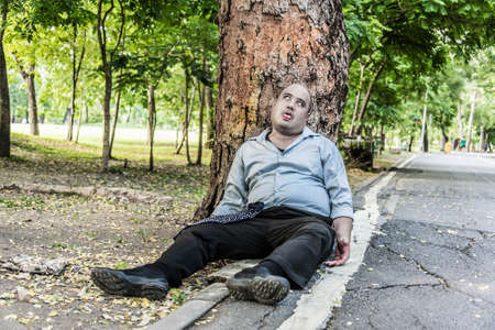 A fat Asian guy corpse die under the tree beside the street  This could use as zomebie concept  Stock Photo