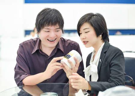 copule: Tailandesa Copule negocios de Asia est�n mostrando expresi�n contenta en su dise�o de producto