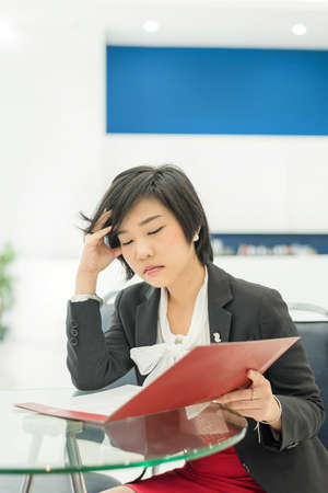 Stress Thai  Asian  businesswoman is reading her document file in office as work photo
