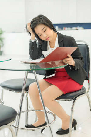 table skirt: Stress Thai  Asian  businesswoman is reading her document file in office as work Stock Photo