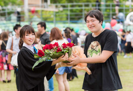 master degree: Thai guy is congratulating his girl friend after graduate her master degree by giving a bouquet Stock Photo