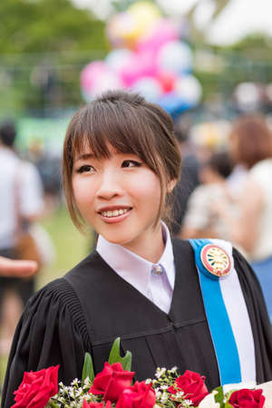 happy moment: Graduate Thai college girl from her master degree in academic gown facial expression for happy moment