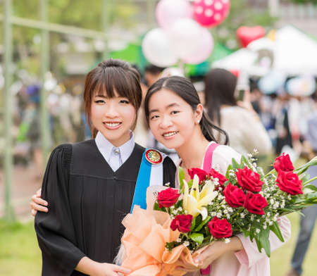 Thai girl is congratulating her friend after graduate her master degree by giving a rose bouquet photo