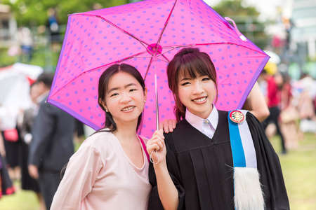 Thai girl graduate college girls are under an umbrella from summer hot weather photo