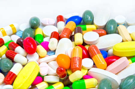 side effect: Pile of pills in white isolated background Stock Photo