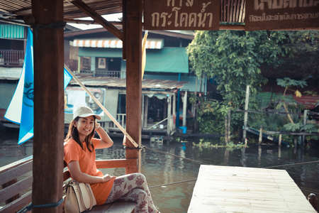 no swimming: Cute Asian Thai girl is relaxing in the pavilion near he riverside in vintage color style. The Thai language say NO FISHING and NO SWIMMING. Stock Photo