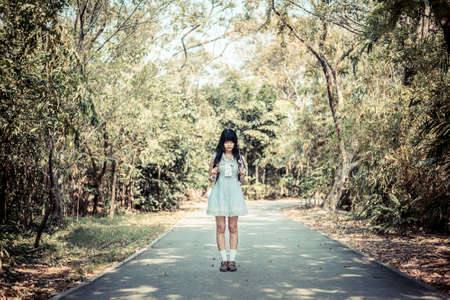 A cute Asian Thai girl is standing on a forest path alone in vintage color style photo