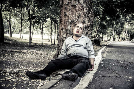 dead trees: A fat Asian guy corpse die under the tree beside the street in rough grain-grunge concept. Stock Photo