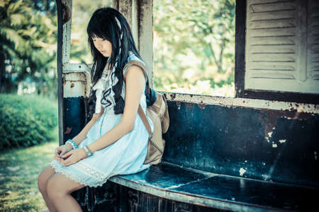 woman stop: Cute Asian Thai girl in vintage clothes is waiting alone in an old bus stop in vintage color tone
