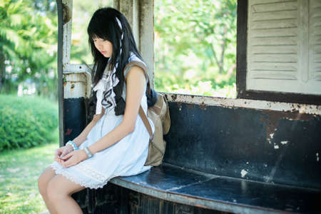 sexy school girl: Cute Asian Thai girl in vintage clothes is waiting alone in an old bus stop