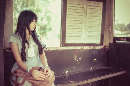 Cute Asian Thai girl in vintage clothes is waiting alone in an old bus stop in bright vintage color tone