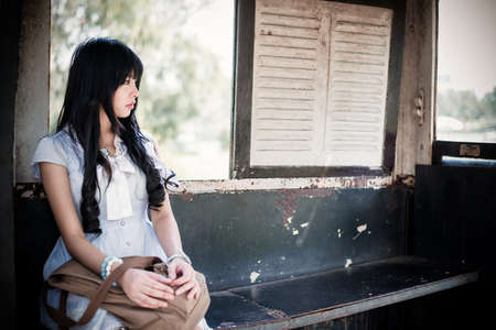 sexy school girl: Cute Asian Thai girl in vintage clothes is waiting alone in an old bus stop in retro color tone Stock Photo