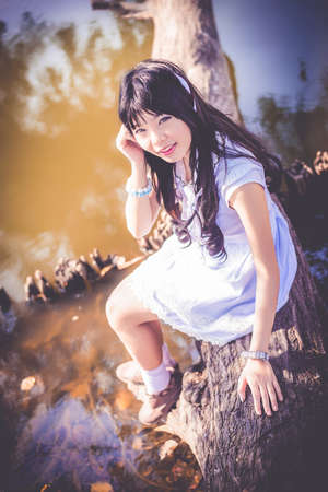 riverside tree: A cute Asian Thai girl is sitting on a tree trunk on the riverside making eye contact in dark vintage style