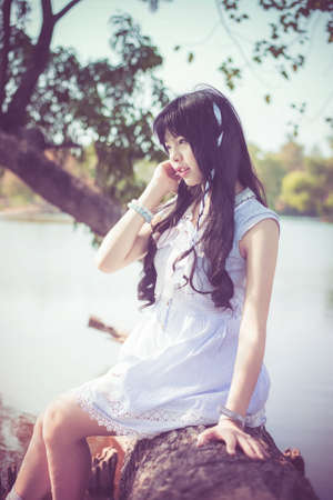 riverside tree: A cute Asian Thai girl is sitting on a tree trunk on the riverside with soft breeze blowing