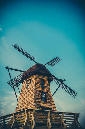 aero generator: Windmill standing in the blue sky creating a nice aerial view in dark vintage color Stock Photo