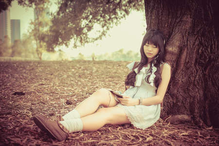 sleeping tablets: A cute Asian Thai girl is leaning on a tree trunk sleeping while listening to the music with earphone on tablet