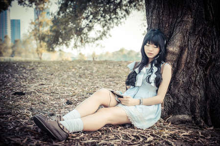 A cute Asian Thai girl is leaning on a tree trunk sleeping while listening to the music with earphone on tablet in vintage color photo