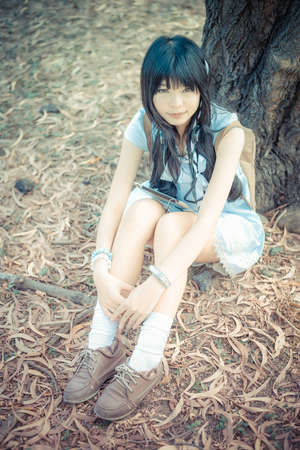 knees up: A cute Asian Thai girl is sitting with her knees up under the tree with her tablet on the laps in vintage color Stock Photo