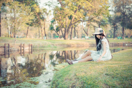 rest in peace: A cute Asian Thai girl is relaxing near the pond in the wilderness in soft vintage color