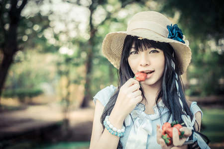A cute Asian Thai girl with vintage clothings is eating strawberry she picked up in the forest in fashion vintage color