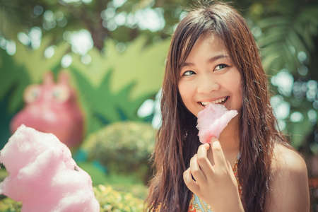 Cute Thai girl is eating pink candyfloss with joy in vintage color photo