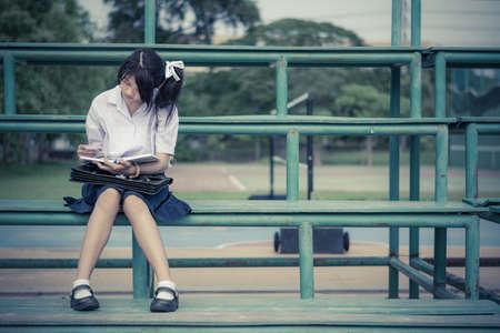 diligente: Colegiala tailandés linda está sentado y leyendo en un stand en el color de la vendimia Foto de archivo