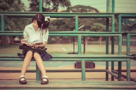 thai student: Cute Thai schoolgirl is sitting and reading on a stand in vintage color