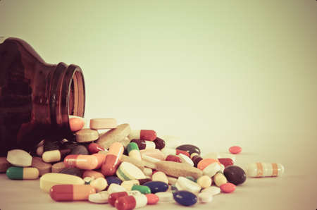 vitamins pills: Many type of drugs poring from the bottle with isolation background with vintage color