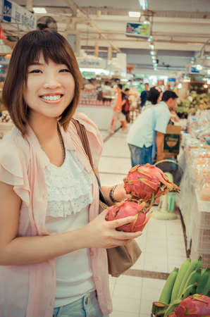 merchant: Active Asian tourism is choosing Pitaya fruit (Dragon fruit) in Thailand open market in vintage color