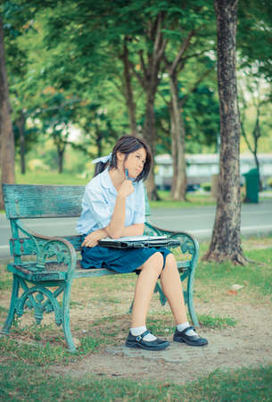 zapatos escolares: Colegiala tailandés linda está estudiando e imaginar algo en un banco en el color de la vendimia, dejando que fluya su mente con imaginación.
