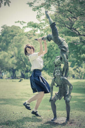 thai teen: Cute Thai schoolgirl is jumping with a statue in the park in vintage color