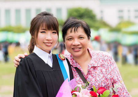Mother is hugging her daughter for her master degree graduation photo