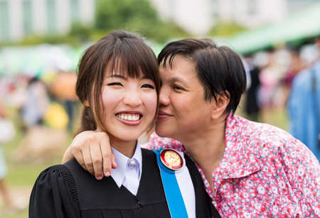 Mother is kissing her daughter with joy for her master degree graduation photo