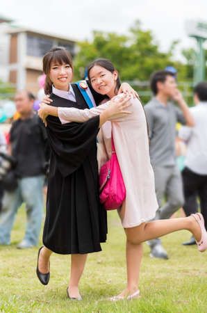 Thai girl is hugging her friend who graduated a master degree photo