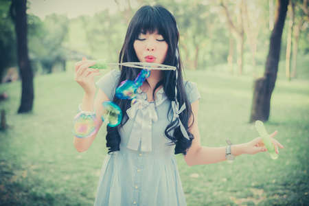 Cute Asian Thai girl is blowing a soap bubbles in the park in dreamy color photo