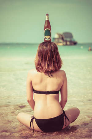 Sexy Asian Thai girl is sitting in the salt water on the seashore with bottle on her head in vintage color Stock Photo